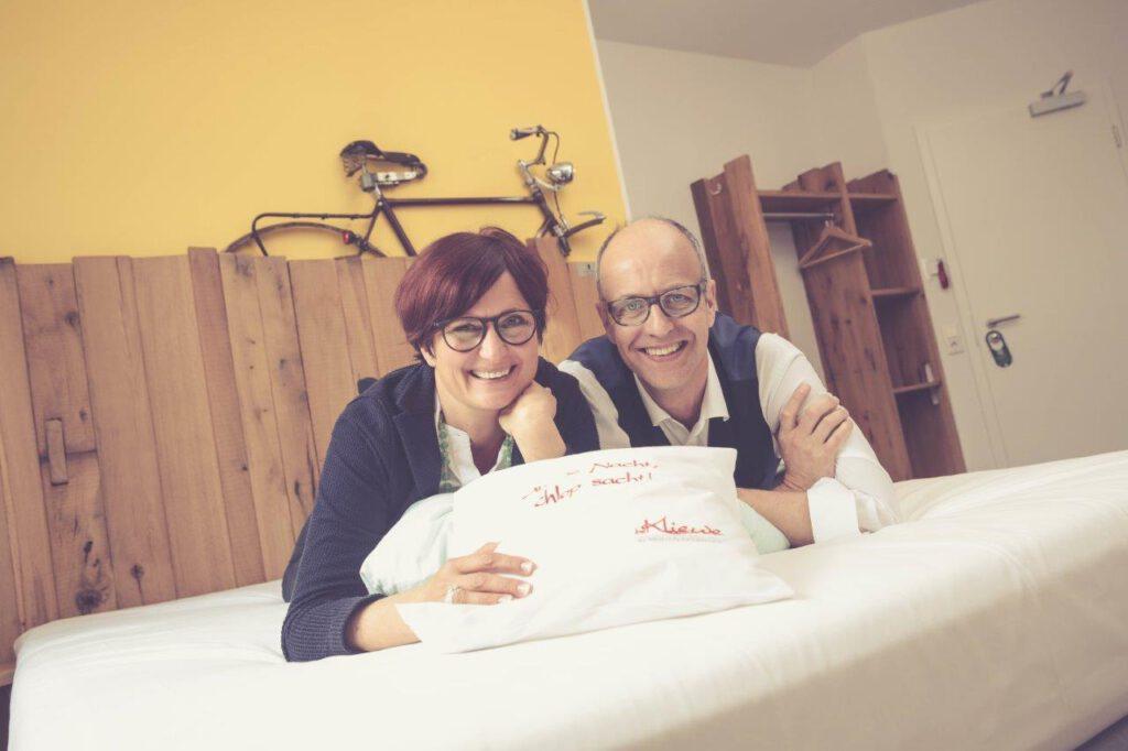 Inhaber Sabine & Thomas Kliewe in einem der 20 individuell eingerichteten Zimmern auf dem Bett