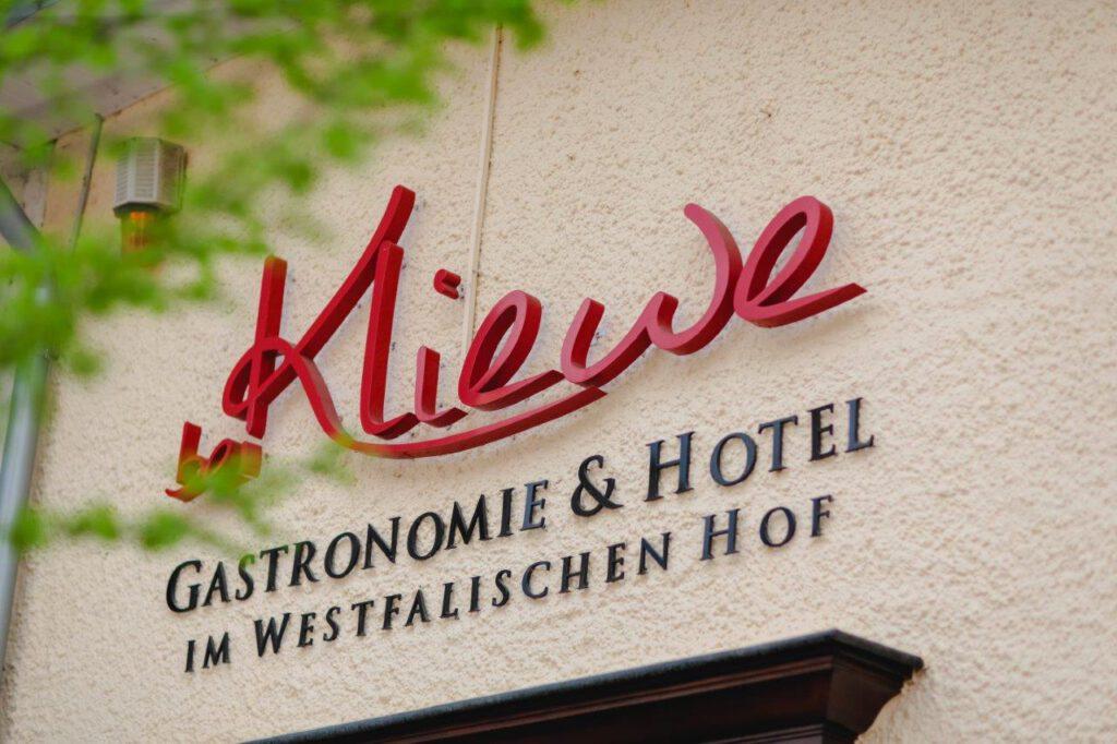 Logo Kliewe an der Außenfassade des Gebäudes in Beckum, in rot Kliewe, in schwarz drunter Gastronomie & Hotel im westfälischen Hof
