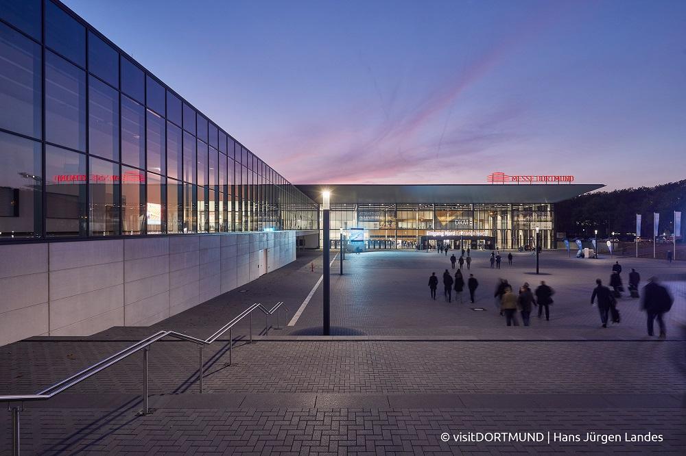 Zu sehen ist der belebte Messevorplatz, sowie der Eingang Nord der Dortmunder Messe am Abend.