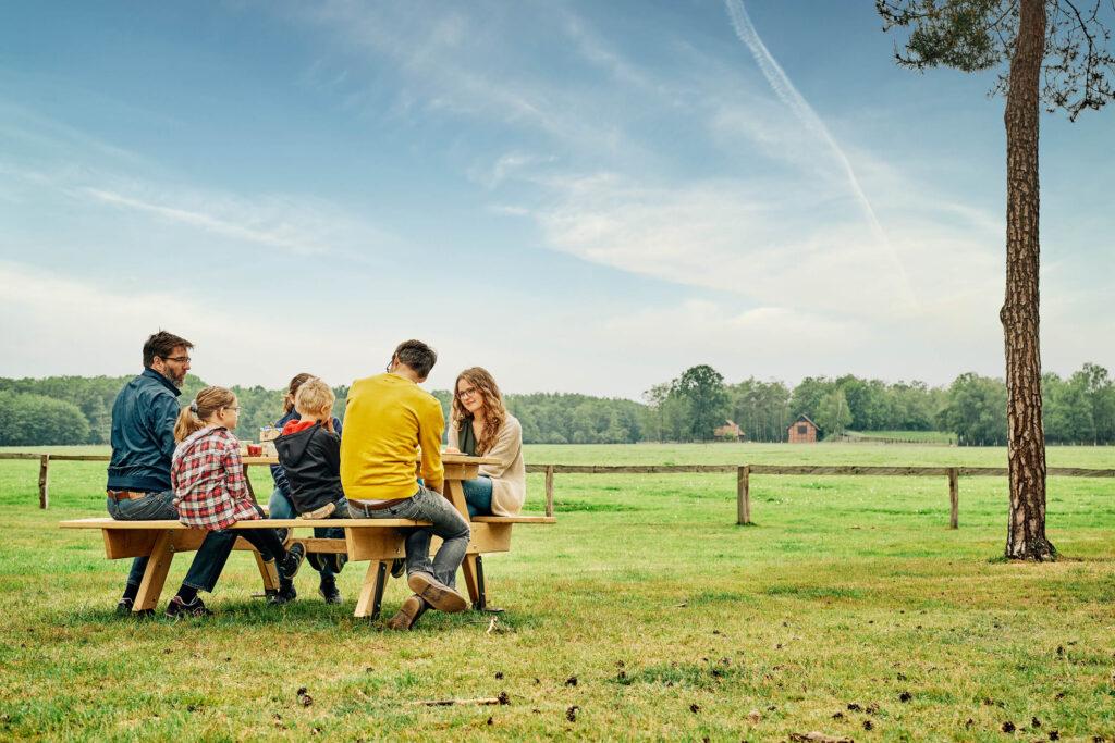 Das Bild zeigt eine Familie am Picknicktisch.