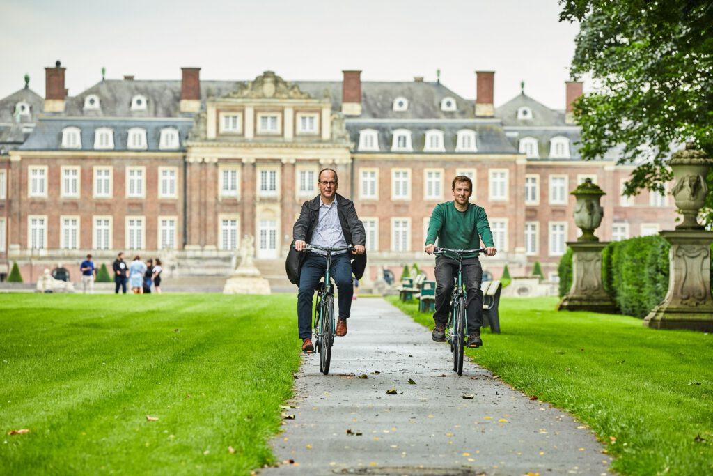 Zu sehen sind zwei Radfahrer vor der Kulisse des Schlosses in Münster.
