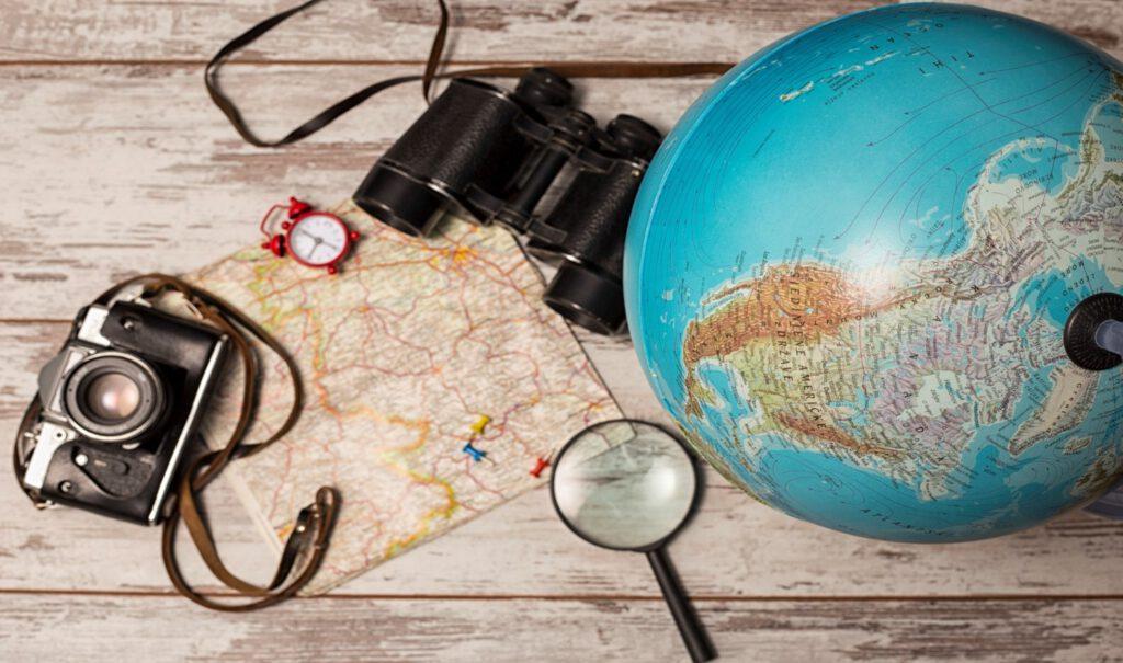 Landkarte, Globus, Fernglas, Fotoapparat und Lupe auf einem Tisch liegend