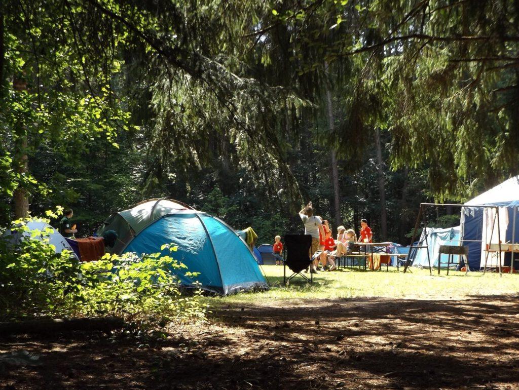 Zu sehen ist ein entspannte Sitaution aus einem Campingplatz mit Familien.