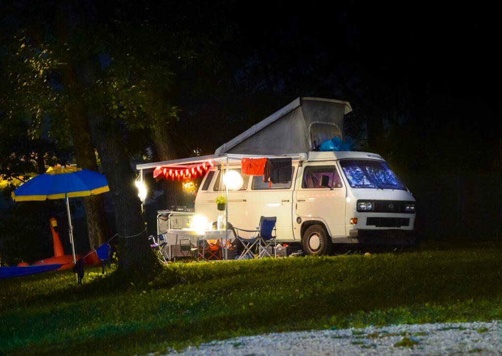 Zu sehen ist eine Nachtszene auf einem Campingplatz mit einem erleuchteten Wohnmobil.