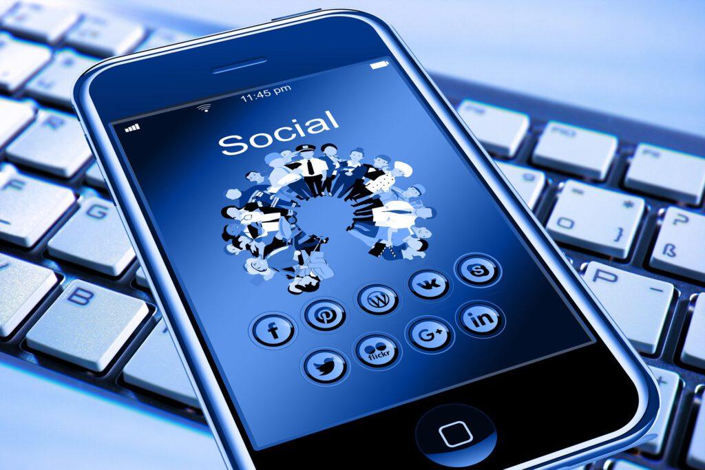 Smartphone mit Icons von Social media Plattformen auf einer Tastatur liegend