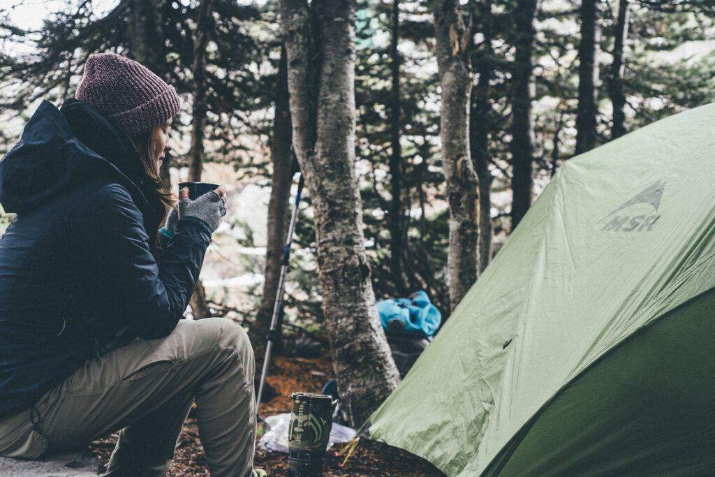 Zu sehen ist eine Campingsituation mit einem Zelt und einer Kochstelle. Eine winterlich gekleidete Frau wärmt sich die Hande an einer Tasse mit einem heißen Getränk.