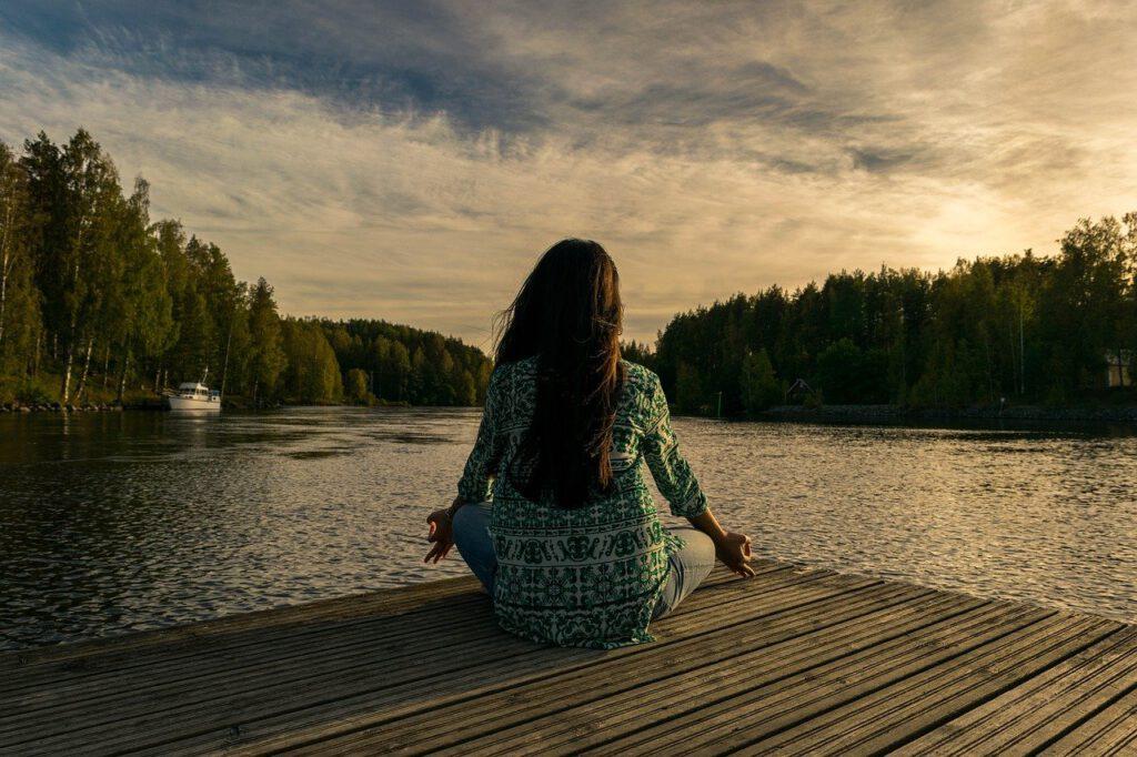 Zu sehen ist eine Frau, die auf einem Steg an einem See meditiert.