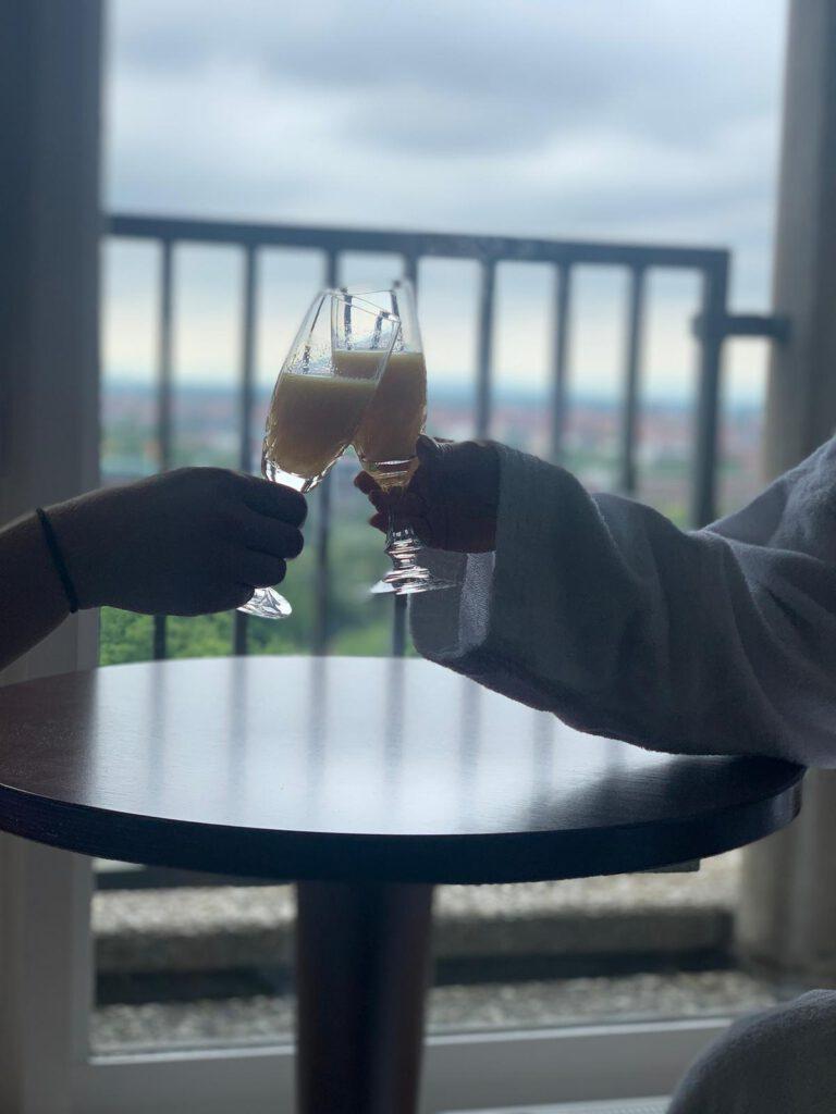 Man sieht zwei Gläser in der Hand von zwei Personen, die anstoßen.