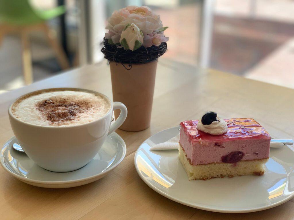 Zu sehen sind eine Tasse Cappuccino und ein Stück Erdbeertorte.